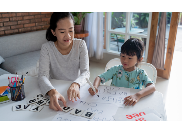 A mother works on phonics with her child.